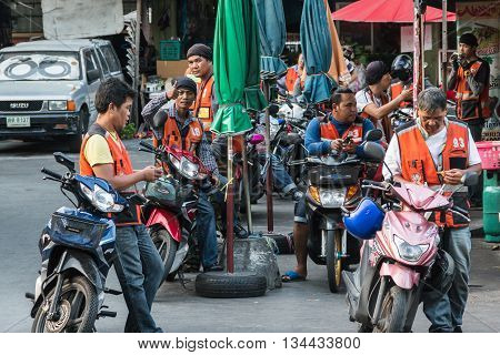 BANGKOK THAILAND - MAY 2 2016 : orange jacket motorbike taxi queue at Huay Kwang market in Bangkok