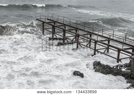 Iron pier at storm. Sea in the storm washes the old iron pier.