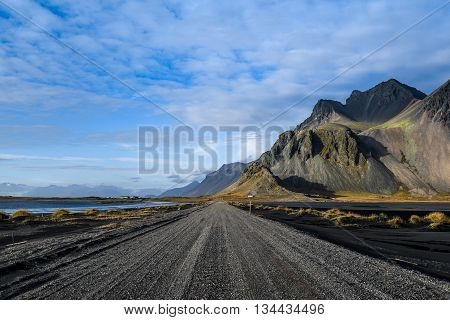 Road mountain and black volcanic lava sand dunes by the sea of Stokksness Southeast Iceland