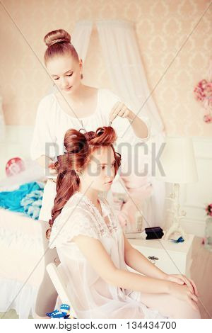Hair stylist makes the bride on the wedding day