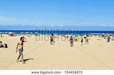 BARCELONA, SPAIN - MAY 30: People playing beach football and sunbathing at La Barceloneta Beach on May 30, 2016 in Barcelona, Spain. This beach hosts about 500,000 visitors during the summer season
