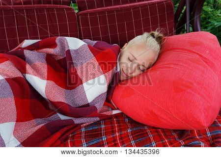 young woman slip on big soft swing in garden on red pillow covered by red checkered blank horizontal close up