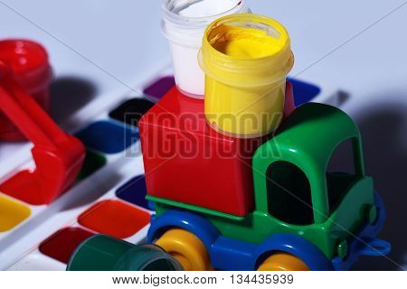 Plastic toy car with set of watercolor and gouache paints palette on grey background closeup