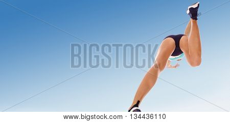 Low angle female athlete jumping against scenic view of blue sky