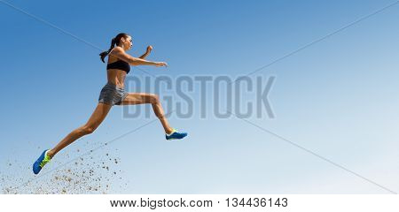 Profile view of sportswoman jumping against scenic view of blue sky