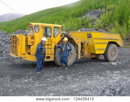 Employees of the gold mining company near the big yellow dump truck with a full body of rubble.