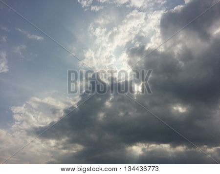Blue sky with dark clouds and sunlight before storm
