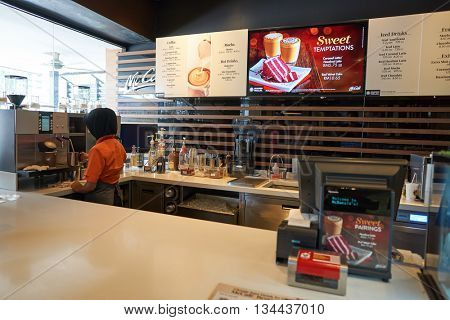 KUALA LUMPUR, MALAYSIA - MAY 09, 2016: barista preparing coffee in McCafe. McCafe is a coffee house style food and drink chain, owned by McDonald's.