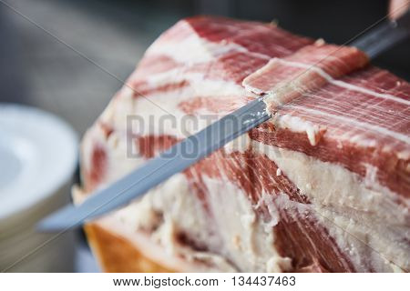 Chef slices serrano ham. Jamon Serrano. Typical Spanish delicatessen. Shallow dof