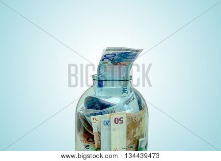 European currency folded into a large glass jar