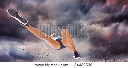 Low angle female athlete jumping against gloomy sky