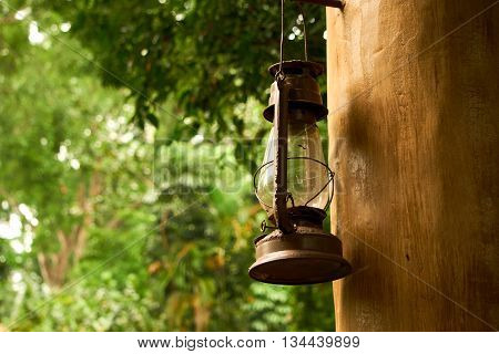 the old style lamp hanging on the wooden pillar