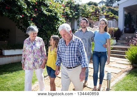 Multi-generation family walking together on the garden path