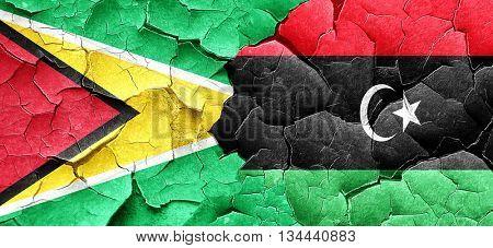 Guyana flag with Libya flag on a grunge cracked wall
