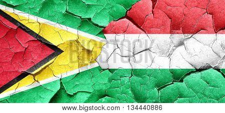 Guyana flag with Hungary flag on a grunge cracked wall