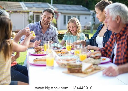 Happy multi-generation family eating at table in back yard