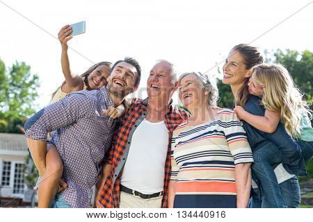 Cheerful girl taking selfie with multi-generation family in back yard