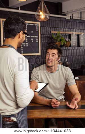 Waiter and customer talking in a coffee shop