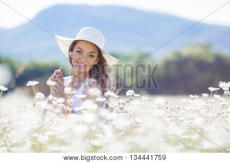 Portrait of beautiful young woman in a white hat with a wide brim, brunette with long curly hair, in a white summer dress,a beautiful smile, on a neck a gold chain, aposing in a white field of blooming daisies in a mountain area