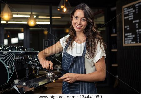 Barista preparing coffee with machine at coffee shop