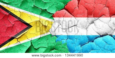 Guyana flag with Luxembourg flag on a grunge cracked wall