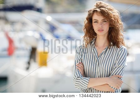 Stylish young woman with gray eyes,curly red hair and sweet smile,dressed in white pants and a bright striped shirt,hanging out on the dock near the yacht club sits amid sea of yachts and boats in summer time in fresh air