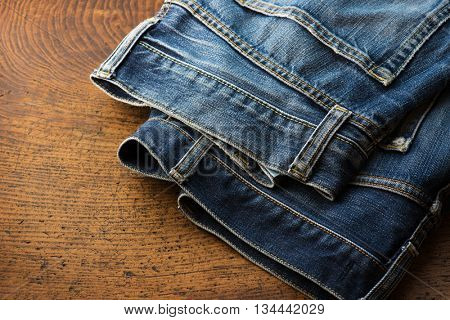 Old pair of nicely faded blue jeans on rustic table.