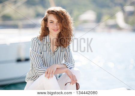 Stylish young woman with gray eyes,curly red hair and sweet smile, dressed in white pants and a bright striped shirt, hanging out on the dock near the yacht club sits amid sea of yachts and boats in summer time in fresh air