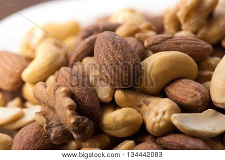 Mixed nuts on a white dish close up. Almond, walnuts, and cashew nuts on plate. shallow depth of field.