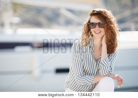 Stylish young woman in dark sun glasses,curly red hair and sweet smile, dressed in white pants and a bright striped shirt, hanging out on the dock near the yacht club sits amid sea of yachts and boats in summer time in fresh air