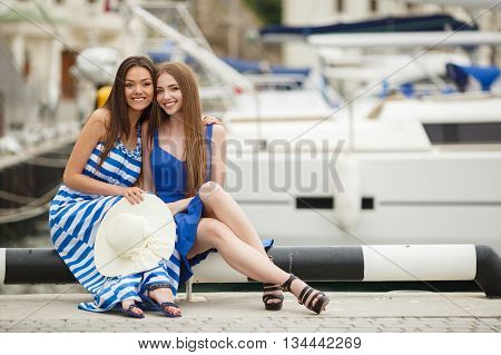 Two young beautiful woman brunette with long straight hair,cute smile,dressed in tunics of blue and blue-white stripe,in hand at one of the bridesmaids-a large white straw hat ,posing at the Harbor, sitting on a background of white yachts and boats