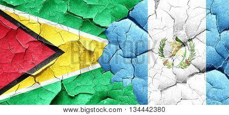 Guyana flag with Guatemala flag on a grunge cracked wall