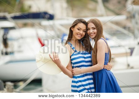 Two young beautiful woman brunette with long straight hair,cute smile,dressed in tunics of blue and blue-white stripe,in hand at one of the bridesmaids-a large white straw hat ,posing standing in the Harbor against white yachts and boats