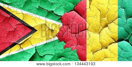 Guyana flag with Guinea flag on a grunge cracked wall