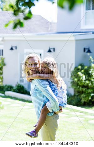 Happy mother piggy-backing daughter in yard against house