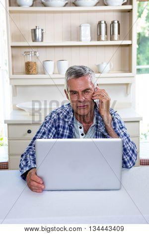 Thoughtful senior man talking on phone while sitting at kitchen