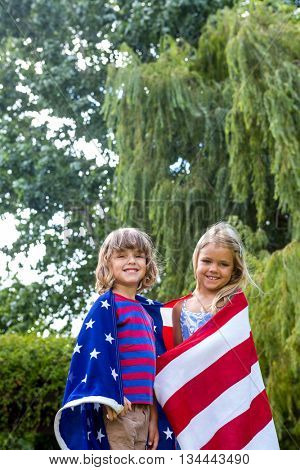 Portrait of happy siblings wrapped in American flag at back yard