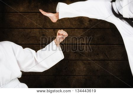 Fighter performing karate stance against dark fence