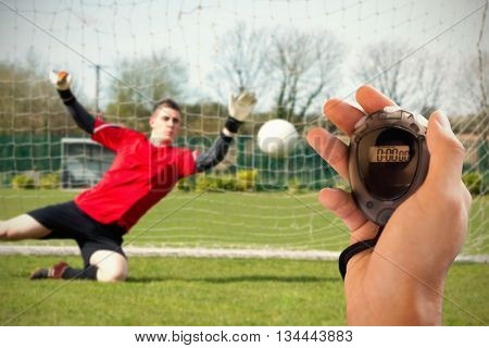 Composite image of coach is holding a stopwatch against goalkeeper in red ready to make a save