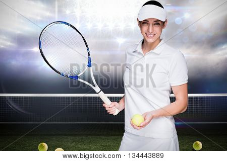 Female athlete posing with a tennis racket against sports pitch