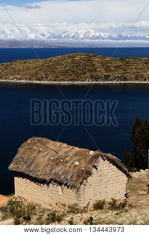 South America Bolivia - Isla del Sol on the Titicaca lake the largest highaltitude lake in the world. Traditional house built of clay relating to snowy mountains