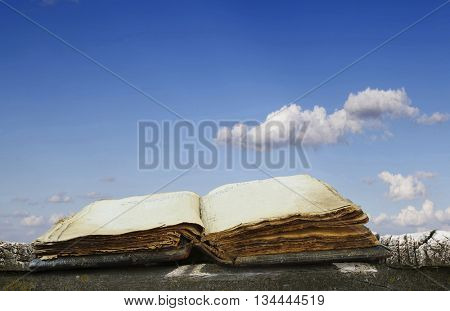 old book on a wooden platform against the sky