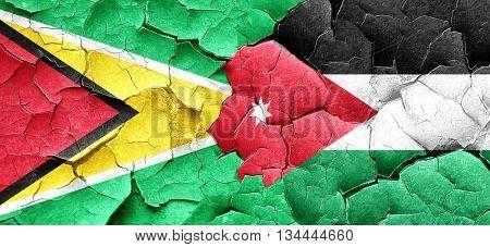 Guyana flag with Jordan flag on a grunge cracked wall