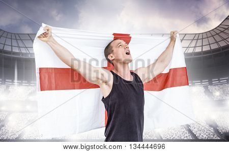 Athlete holding england national flag against sports arena