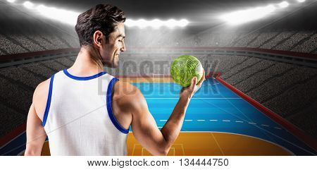 Happy athlete male holding a ball against digital image of handball field indoor