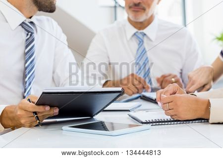 Mid section of businessmen and businesswomen discussing at his desk in the office