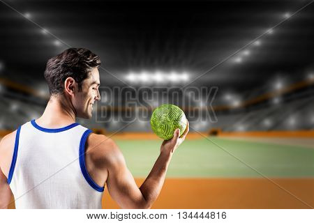 Happy athlete male holding a ball against handball field indoor