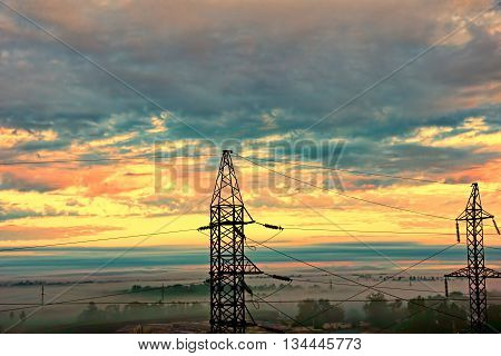 Two electricity pylons against of dramatic sunset sky taken closeup.