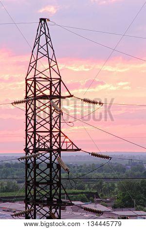Electricity pylon on cloudy sunset sky background taken closeup.