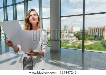 Businesswoman hold some documents against a big window